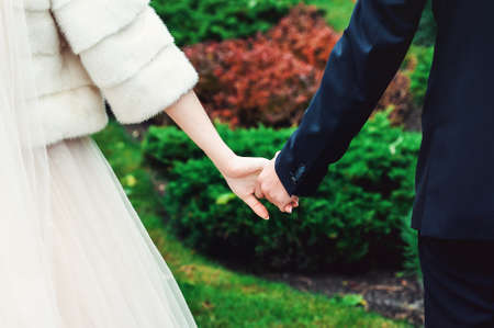 Bride and groom holding hands on a green background. Wedding day
