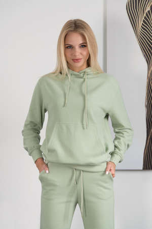 Stylish beautiful young blond woman in a green tracksuit poses near a white wall in the room.