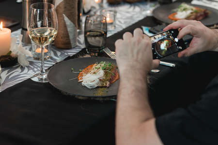 man taking pictures of a Grilled tuna steak with onion on a gray ceramic plate. Selective focus, close-up.