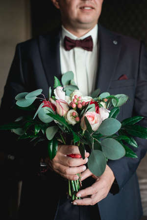 Man is holding a wedding colorful bouquet. Beauty of colored flowers. Close-up bunch of florets. Bridal accessories. Female decoration for girl. Details for marriage and for married couple Фото со стока
