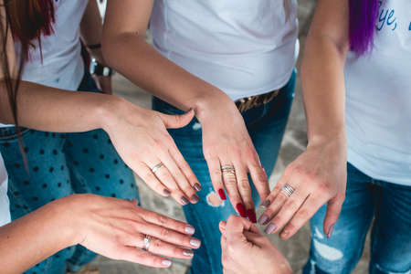 Young girls girlfriends in white T-shirts and jeans folded their arms at each other and show manicure and rings. Team building women in nature. Bachelorette party