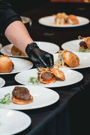 chef in a black gloves serving a burgers on the table in a restaurant. Black tablecloth Banco de Imagens