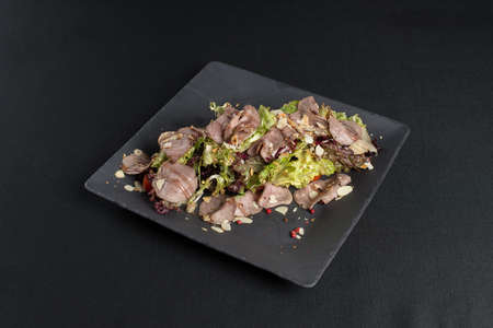 Salad with smoked duck meat, sweet and sour sauce with almonds flakes on a black ceramic plate