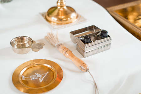 Set of priest for conducting the baptism ceremony on a white tablecloth in the Church. Selective focus