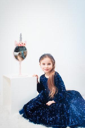 Little cute girl with light blue eyes in a dark blue dress near small mirror