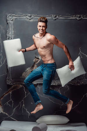Smiling man with two white pillows in hands jumping on a mattress on a gray background. Concept of comfortable sleep. orthopedic mattress and pillow Foto de archivo