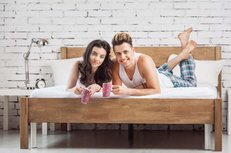 Joyful couple drinking a cup of tea lying on their bed at home