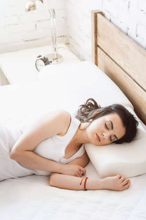 Woman sleeping on a white pillow and a mattress on a wooden bed. Concept of comfortable sleep. orthopedic mattress and pillow