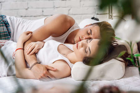 Young loving couple sleeping in pajamas in the bed