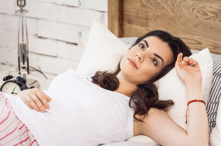 Girl lying on a white pillow and a mattress on a wooden bed. Concept of comfortable sleep. orthopedic mattress and pillow