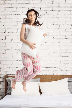 Girl with a white pillows in hands jumping on a bed, white bricks background. Concept of comfortable sleep. orthopedic mattress and pillow