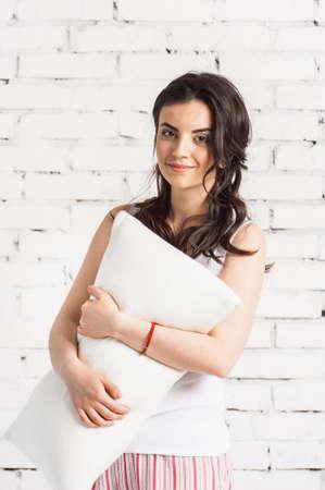 Woman holding a white pillow, white bricks background. Concept of comfortable sleep.