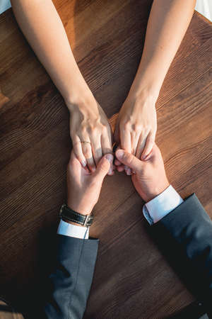 Loving couple siting at the round wooden table, gently holding hands. High angle view Foto de archivo