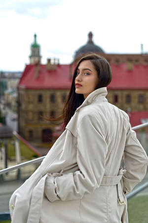 Outdoor portrait of a young beautiful fashionable lady wearing stylish coat . Model looking aside. Female fashion concept. City lifestyle. Close up.