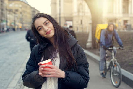 Stylish Caucasian woman in a coat stands and drinks coffee on the street. Urban style and fashionable girl with a red paper cup of coffee.