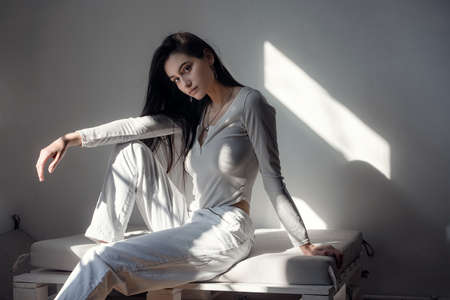 portrait of beautiful gentle woman in a white bodysuit posing in the sunshine. Black long hair. sensuality and tenderness Foto de archivo