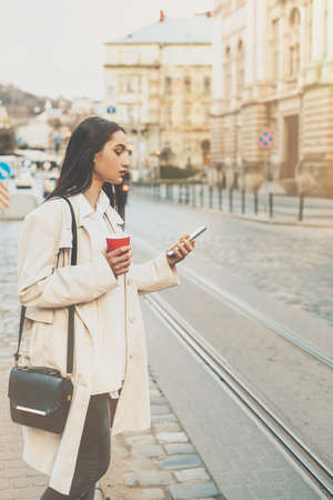 A woman on the street uses a mobile phone. online shopping. use of mobile applications.