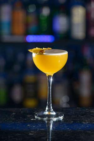 yellow refreshing cocktail on a bar desk Standard-Bild