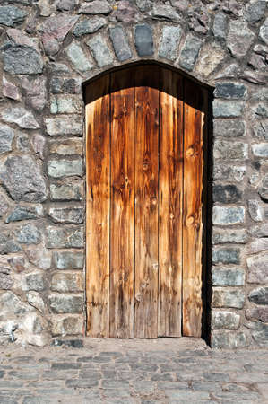 old wood door in a stone wall of an ancient building of an abandoned mountain village photo
