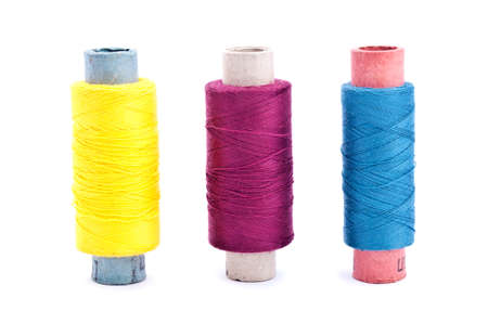 Three vintage paper multi colored thread coils on white background (blue, yellow and lilac) photo