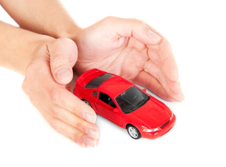 Rode auto in handen op een witte achtergrond. Concept van veilig rijden Stockfoto