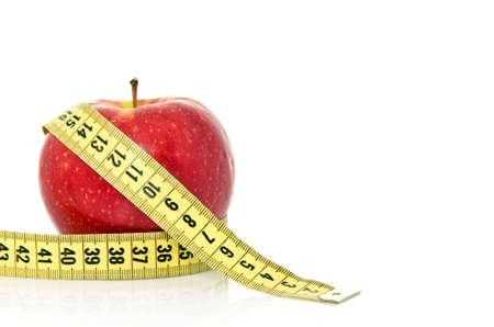 cinta metrica: Manzana roja fresca con cinta sobre fondo blanco (concepto de salud y la dieta)