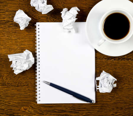 Pen on a white paper with cup of coffee on dark desk Stock Photo