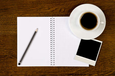 blank notebook with photo frame and coffee cup on wooden background photo