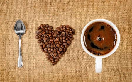 tomando refresco: Forma de coraz�n hecho de granos de caf� con una cuchara y una taza de caf� sobre la ortograf�a de arpillera Me encanta el caf�