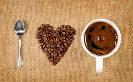 Heart shape made from coffee beans with a spoon and cup of coffee on hessian spelling I love coffee  Stock Photo