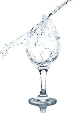 overflowing: Pouring water into glass isolated on white background