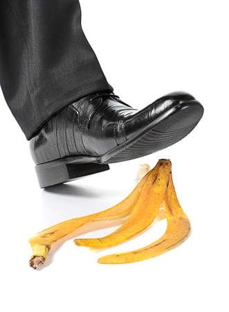 hombre cayendo: Empresario pies a punto de resbalar y caer en una c�scara de pl�tano en el fondo blanco Foto de archivo