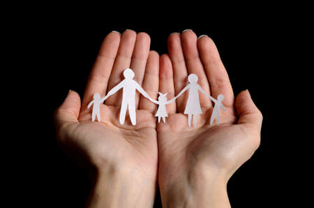protect family: Cutout paper chain family with the protection of cupped hands, concept for security and care on black background