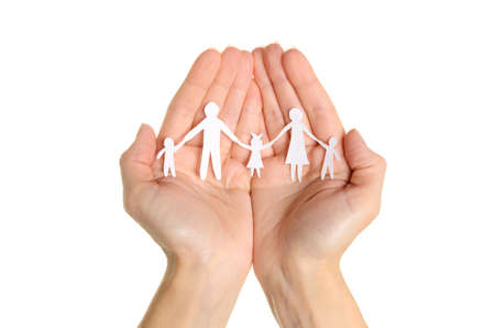 Cutout paper chain family with the protection of cupped hands, concept for security and care on white background photo