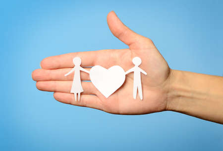 Paper family in hand on blue background  photo