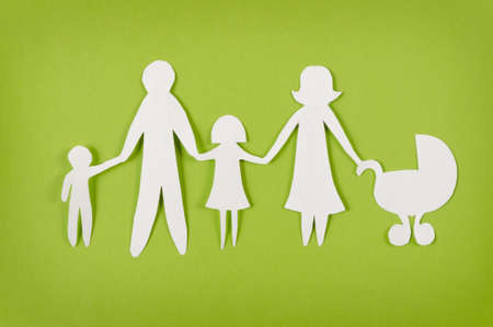 Closeup of happy paper family on green background