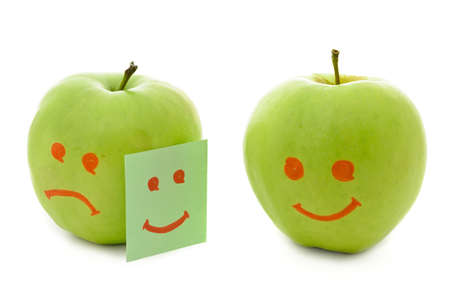 Two green apples, smiling and crying on white