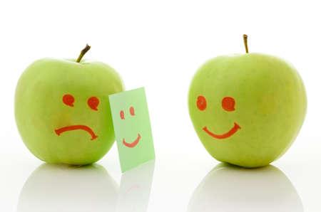 desprecio: Dos manzanas verdes, sonriendo y llorando en blanco