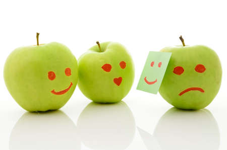 Three green apples, smiling and crying on white