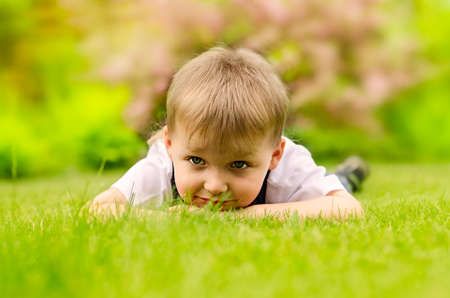 Little boy lying on a green grass  photo