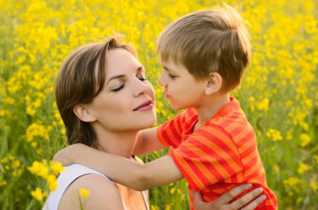 Happy woman with child outdoors in rapeseed field in bloom