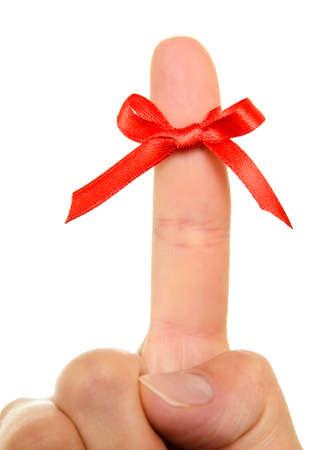Hilo rojo atado alrededor de los dedos como un recordatorio, aisladas sobre fondo blanco.