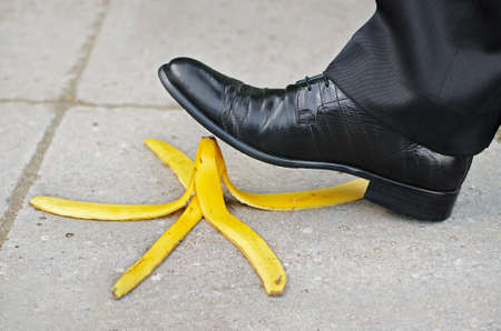 slippery: Businessman about to slip and fall on a banana skin