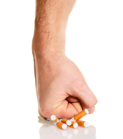 no problems: Mans fist crushing cigarettes isolated on white background