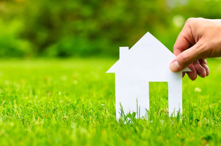 home insurance: Hand hold house against green field  Stock Photo