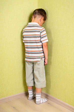 Little child boy wall corner punishment standing  Standard-Bild