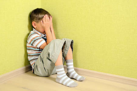 Little child boy wall corner punishment sitting Standard-Bild