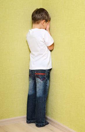 mischief: Little child boy wall corner punishment standing  Stock Photo