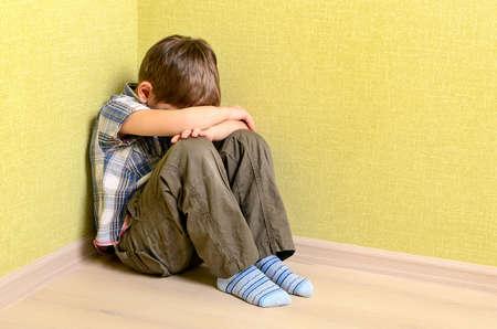 violencia intrafamiliar: Niño pequeño niño sentado pared de la esquina castigo