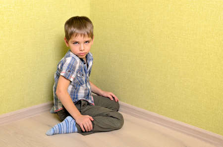 Angry and sad boy sitting in corner